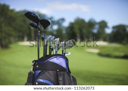Golf bag and clubs in front of de focused green with sand traps