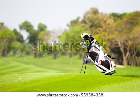 Golf bag is located on fairway in the golf course. #559584358