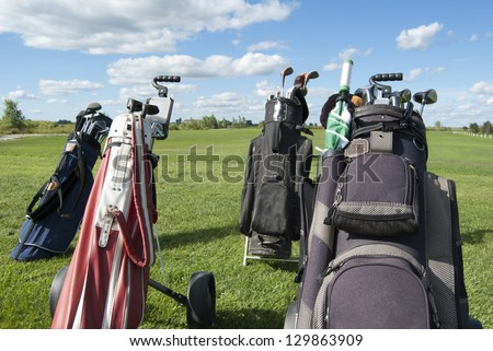 Golf Bags and clubs at a golf course on a sunny day.