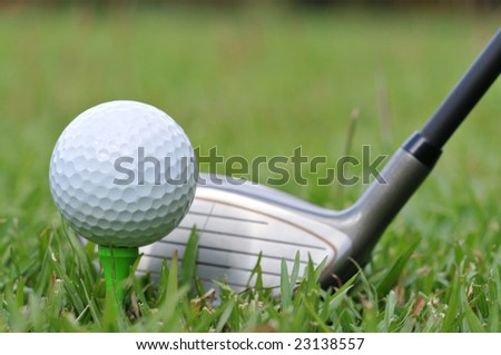 Golf ball and driver on fairway