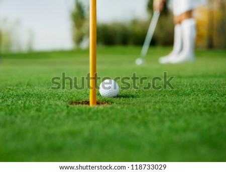 Golf ball and female golfer in background