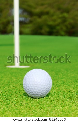 Golf ball and golf hole on the green grass