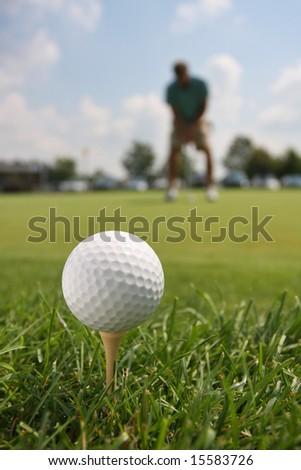 Golf Ball and Golfer Against Blue Sky