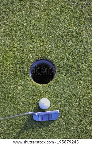 Golf ball and putter on golf green.