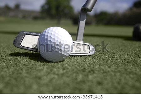 Golf ball and putter on the putting green.