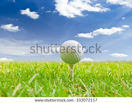 golf ball and tee grass against blue sky