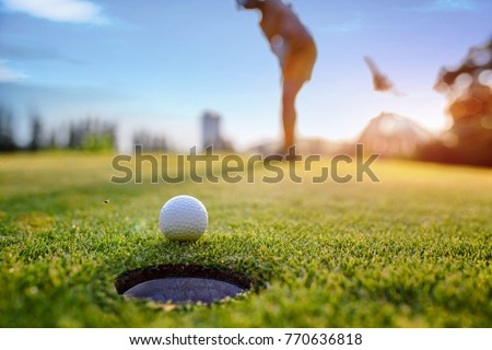 Golf ball approach to the hole on the green, putting by woman golf player in background