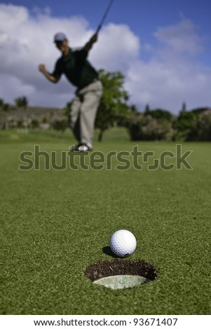 Golf ball approaches hole on the putting green as golfer celebrates in the background.