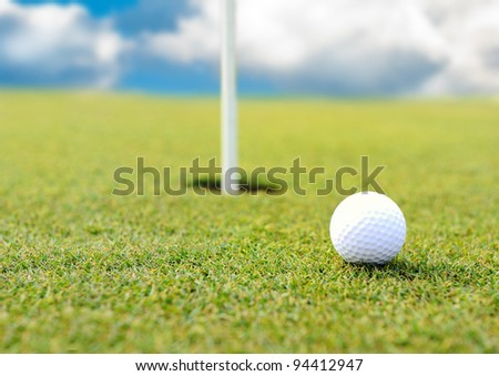Golf ball at hole on grass field