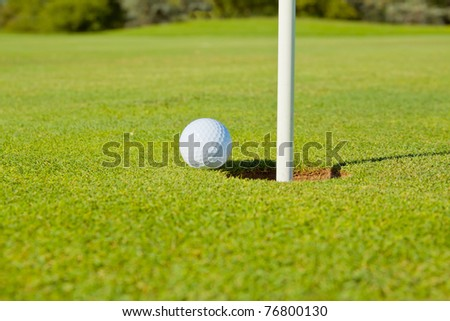golf ball close to (going into) the hole(cup) with the flag still in close up