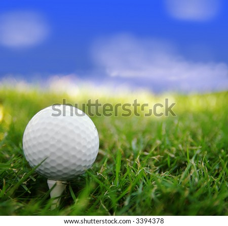 Golf ball closeup, on a tee, and sky