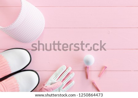 Golf ball, golf glove, tees, golf shoes and golf visor  on a wooden surface in pink, top view, ladies day