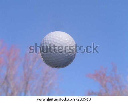 Golf ball in flight - blue sky - trees in background