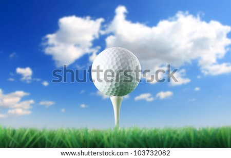 Golf ball in the grass against a  blue sky