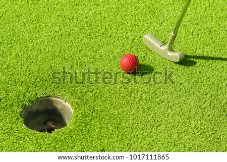 Golf ball is sunk in the hole with a putter while playing minigolf