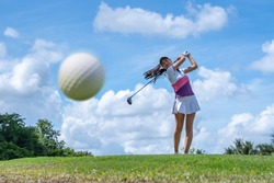 Golf ball just coming off the tee from girl golfer in swing in the morning time