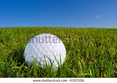 golf ball lies on grass turf with blue sky background - stock photo