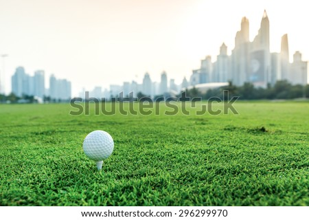 Golf ball lying on the grass in front of Dubai skyscrapers. Golf courses. Players are trained to play golf on the golf course. Close-up view of a golf ball
