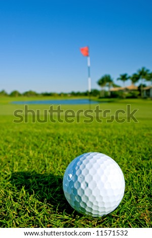 golf ball near green and pin of lovely tropical golf course with clear blue sky - stock photo