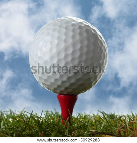Golf ball on a red tee with cloudy blue sky behind