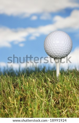 Golf ball on a tee with grass sky.