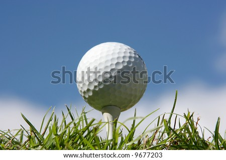 Golf ball on grass against a blue sky and white clouds