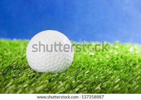 Golf ball on green field grass against blue sky - horizontal image