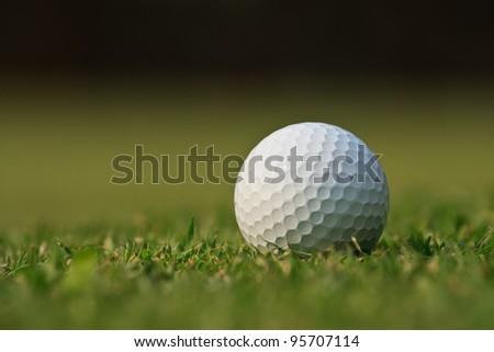Golf ball on green grass with blur background