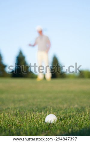 Golf ball on green meadow isolated on golf player. White ball on green tee.