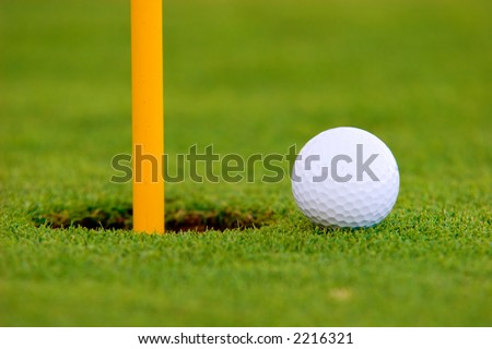 Golf ball on green, near hole.