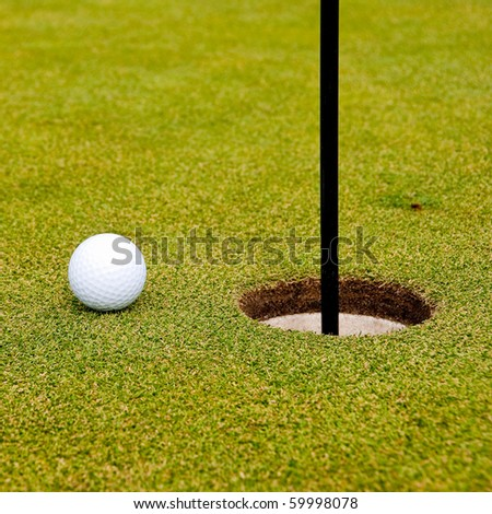 Golf ball on green with a hole. Shallow depth of field. Focus on the ball and the hole.