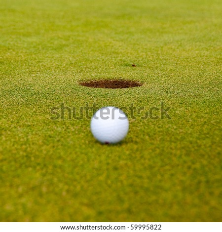 Golf ball on green with a hole. Shallow depth of field. Focus on the hole.
