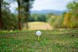 Golf ball on hills for golfer playing sport on vacation time, ball on green golf on tee off, beautiful layout and fairway on field sports, forest and grass lawn landscape on summer