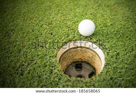 golf ball on lip of golf hole