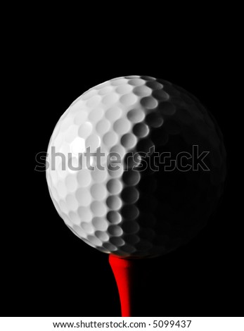 Golf ball on red tee, with black background.