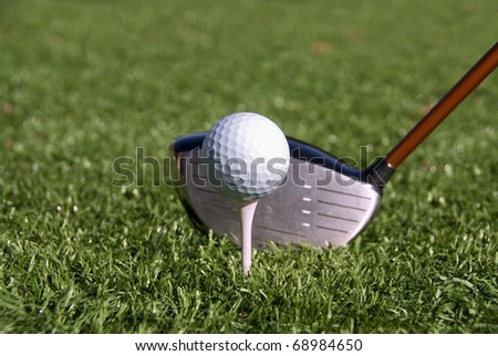 Golf ball on tee about to be hit by a driver.