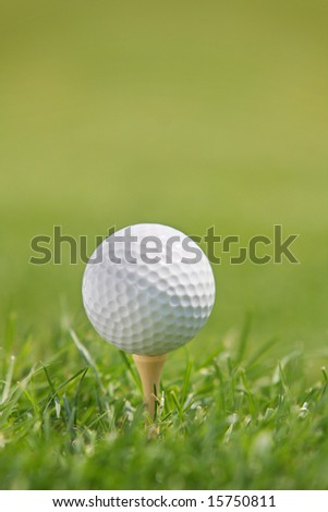 Golf Ball on Tee against green background of blurred  bright green grass.