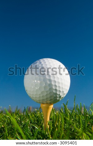golf ball on tee from ground level, deep blue sky for copy