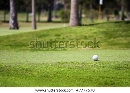 Golf ball on tee in a beautiful green grass golf course. Photographed with shallow DOF (Lifestyle concept)