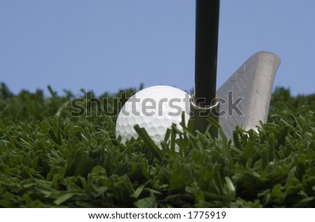 golf ball on tee on grass with blue sky and golf club