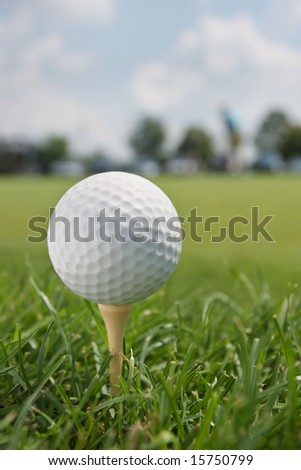 Golf Ball on Tee with blurred fairway and trees in background.
