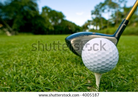 golf ball on tee with driver behind
