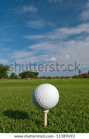 golf ball on tee with fair skies overhead