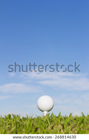 Golf ball on tee with sky background