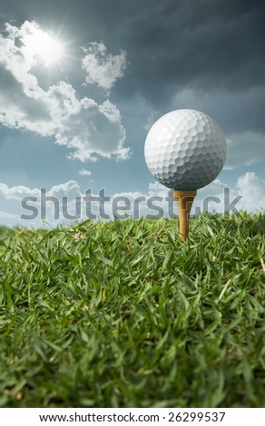 golf ball on tee with sunny day