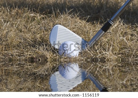 Golf ball on the edge of a water hazard