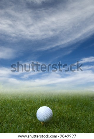 golf ball on the grass with blue sky
