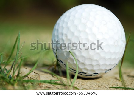 Golf ball partly hidden just outside the green Very shallow depth of field Golf ball in focus