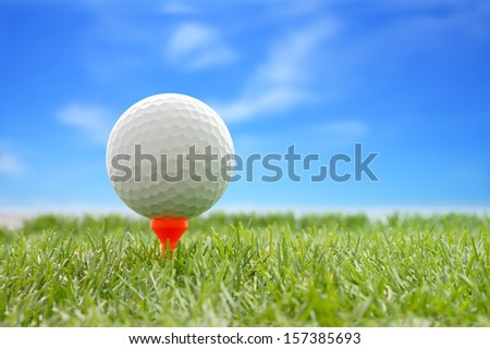 Golf ball plastic tee with blur blue sky.