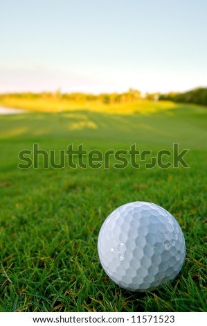 golf ball resting on bunker of lovely golf course with pale blue sky and shallow depth of field